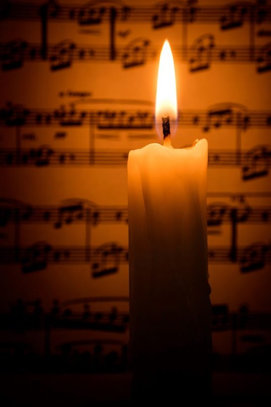 Free stock photo Lit candle with sheet of music in the background