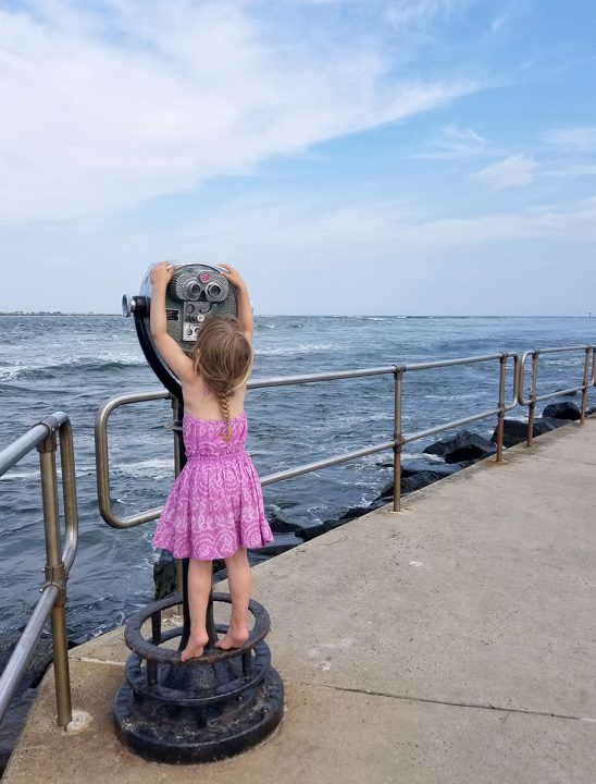Free stock photo Little girl on tip toes trying to reach binoculars to see