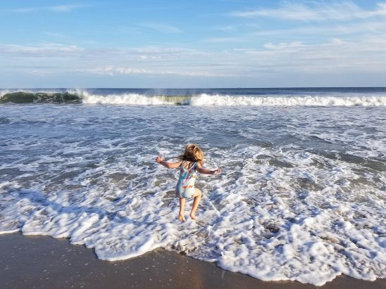 Free stock photo Little girl jumping in the surf.