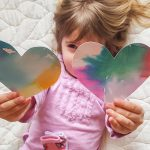 Free stock photo Little girl holding up two colorful cardboard hearts