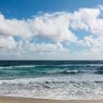 Free stock photo Ocean washing up onto a beach with cumulus clouds in the sky