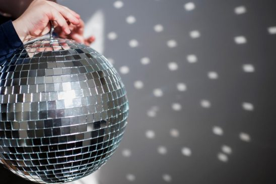Free stock photo Child's hands holding a disco ball reflecting patterns on a wall