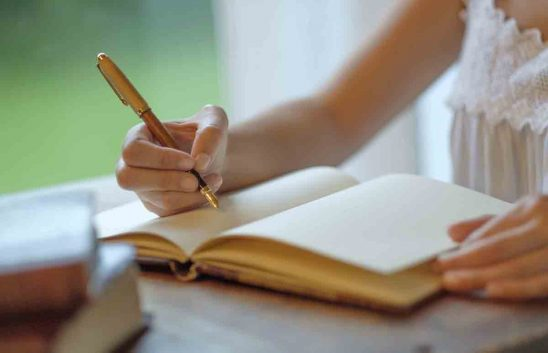 Free stock photo Cropped image of woman writing with fountain pen in book
