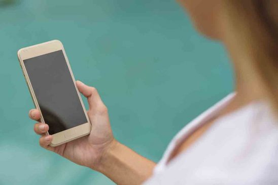 Free stock photo Cropped image of woman holding smart phone with blank screen against sea