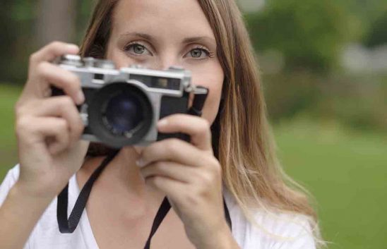 Free stock photo Close-up portrait of woman using old-fashioned camera