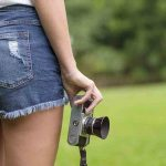Free stock photo Midsection of woman in shorts holding vintage camera in park