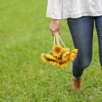 Free stock photo Low section of woman holding gerbera daisies while walking on grass