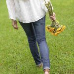 Free stock photo Rear view of woman holding gerbera daisies while walking on grass