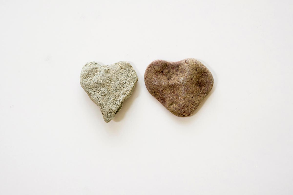 Free stock photo Two heart shaped stones in the middle of a white space