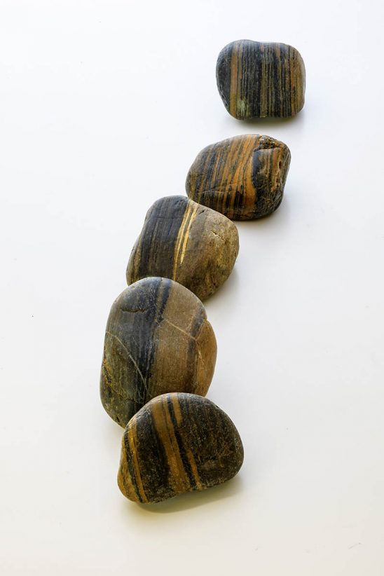 Free stock photo Five striped river stones in a row