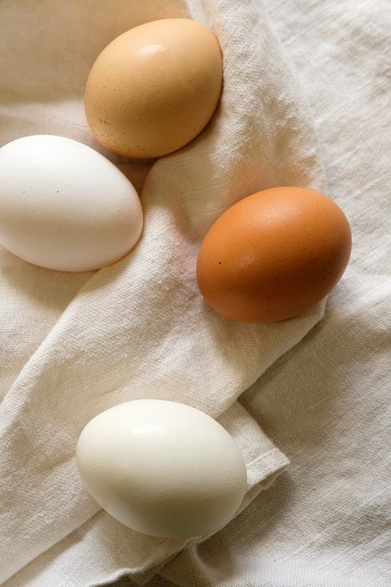 Free stock photo Brown and white eggs on a white table cloth