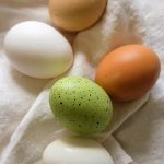 Free stock photo A decorated Easter egg with farm eggs on a white cloth