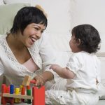 Free stock photo Mother showing her child how to play with toys