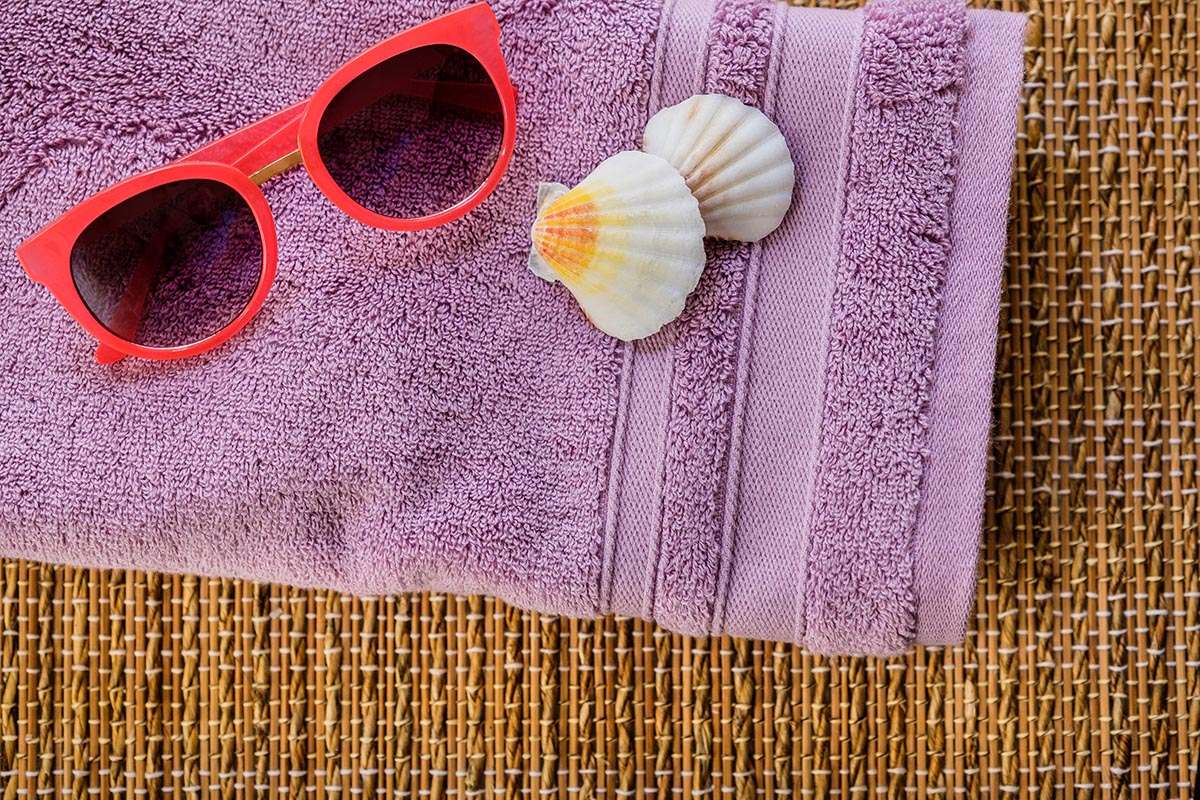 Free stock photo Red sunglasses and seashells resting on a purple towel
