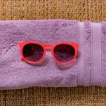 Free stock photo Red sunglasses resting on a purple towel