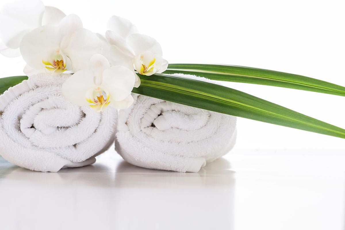 Free stock photo White orchids resting on towels and tropical leaves