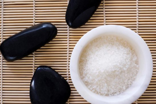 Free stock photo Bowl of bath salts with massage stones on a mat