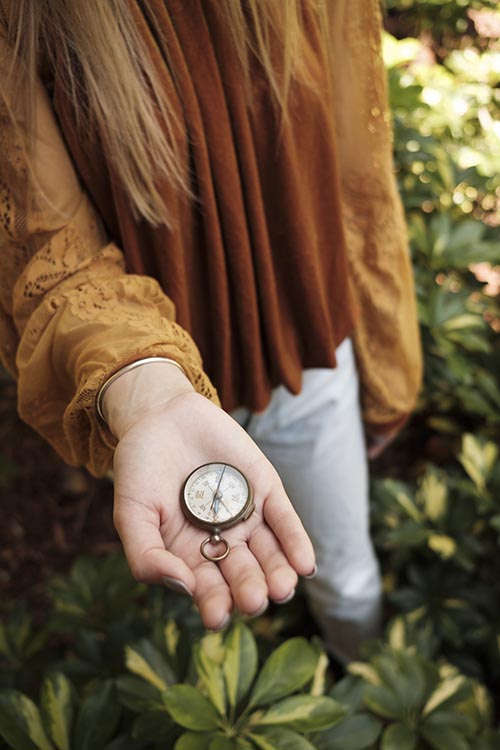 Free stock photo Woman's hand holding a compass in the woods