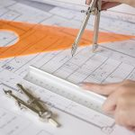 Free stock photo Woman's hands using a drafting compass on architecture plans