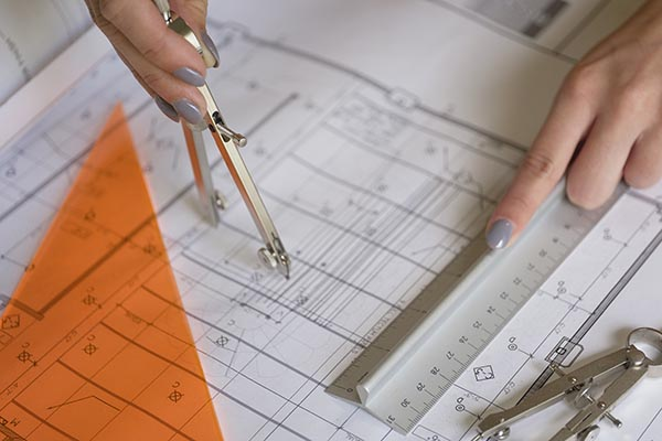 Free stock photo Female architect using a compass to draw on set of plans