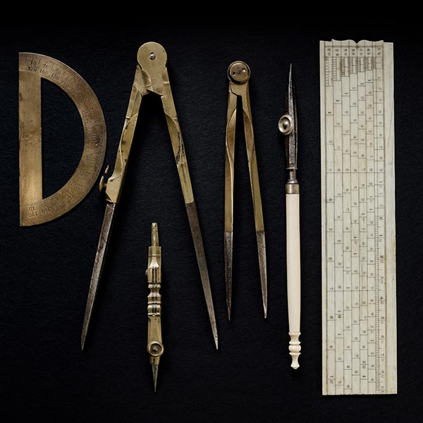 A group of antique brass drafting tools against a black background ...