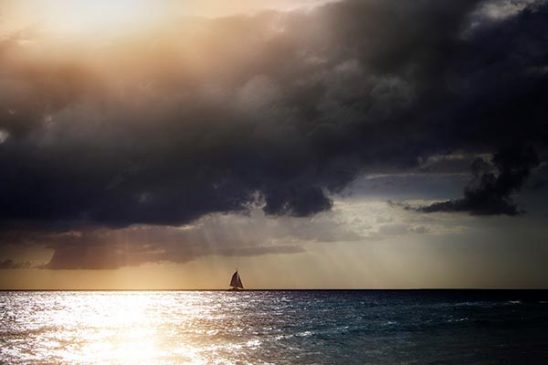 Free stock photo Sailboat on the ocean under storm clouds with sun rays