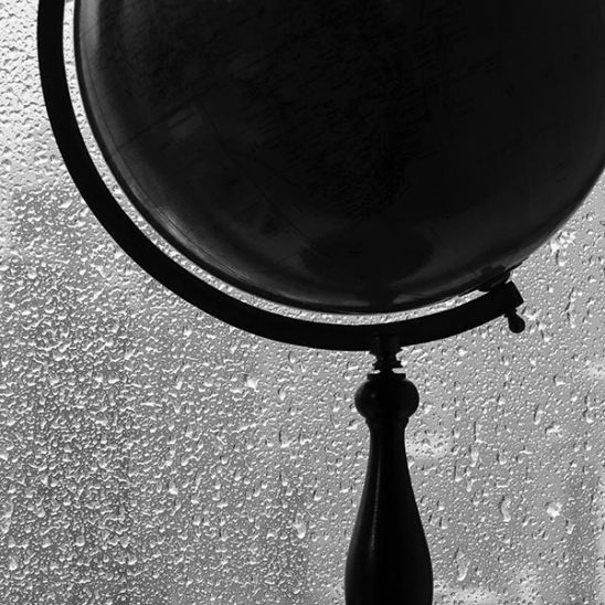 Free stock photo Silhouette of a globe against rain falling on a window