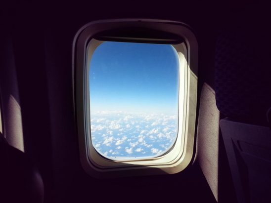 Free stock photo Airplane window with sky and puffy clouds
