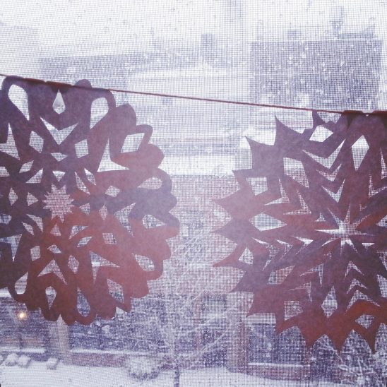 Free stock photo Snowflake pattern cutouts hanging in front of a window with a winter scene