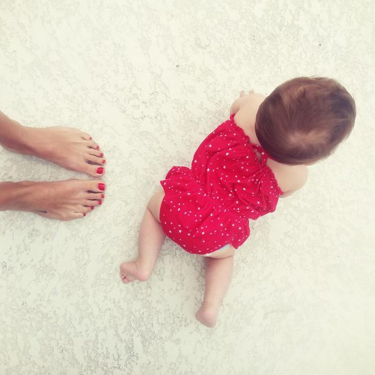 Free stock photo Baby in a red outfit crawling on the floor with mother's feet showing