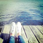 Free stock photo Feet with white sneakers on a dock by a lake