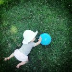 Free stock photo Baby pushing a blue ball on the grass