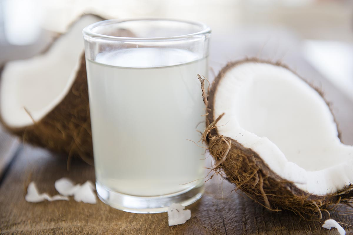Free stock photo Glass of coconut milk with a split coconut