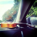Free stock photo Ukulele resting on the dashboard of a car