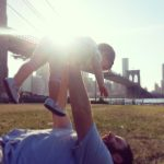 Free stock photo Father on the lawn holding up a baby with the Brooklyn Bridge in the background