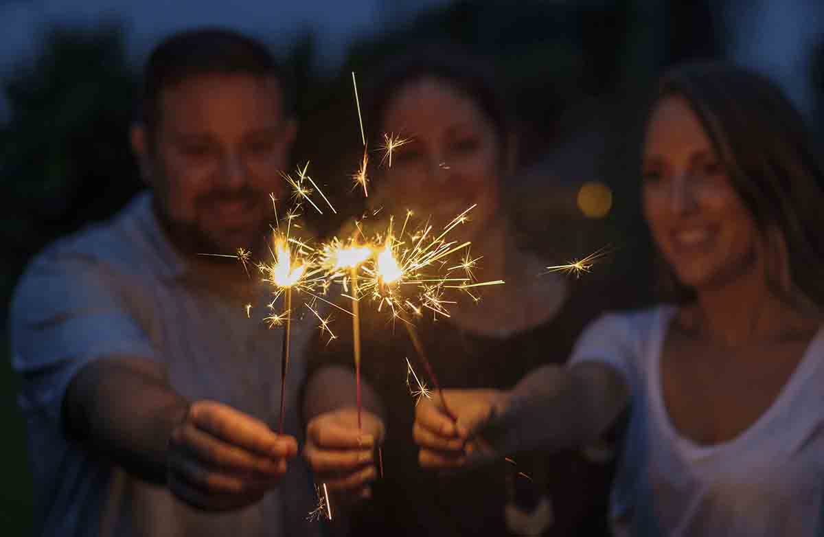 Free stock photo Man and women holding sparklers in park