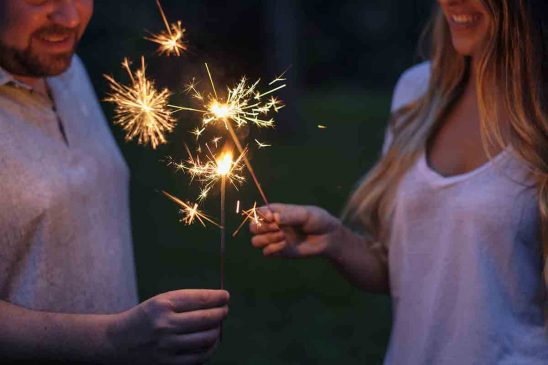 Free stock photo Midsection of man and woman holding sparklers