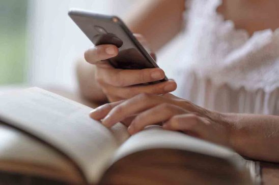 Free stock photo Cropped image of woman using mobile phone while reading book
