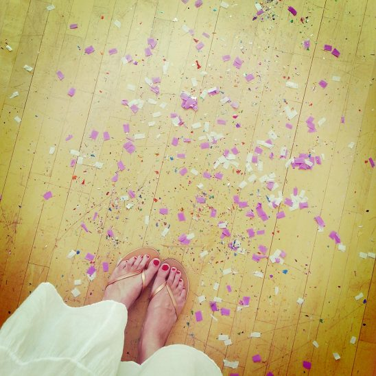 Free stock photo Down angle of woman's feet with red polish next to confetti on a wood floor