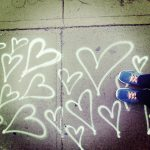 Free stock photo Child's feet next to painted hearts on a sidewalk