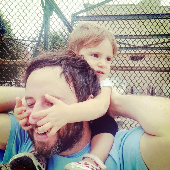 Free stock photo Baby holding father's face while riding on his shoulders