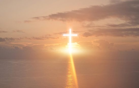 Free stock photo Bright cross lit up in a sunset sky over water