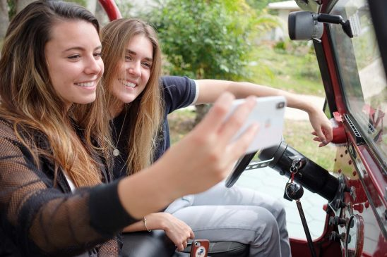 Free stock photo Two young women taking a selfie in an open car