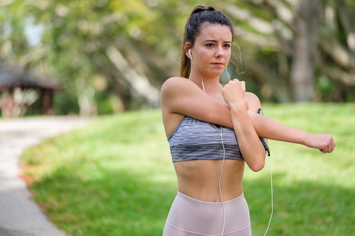Free stock photo Young woman stretching before running