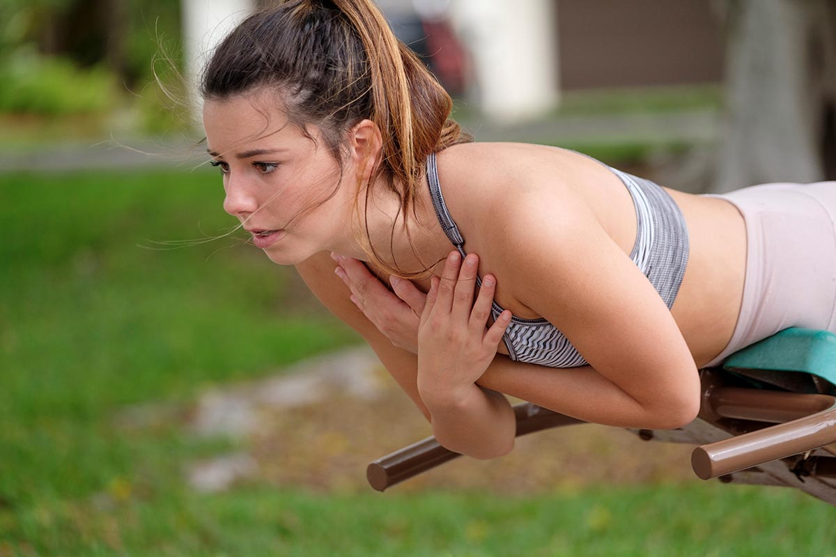Free stock photo Young woman doing abs exercises outdoors