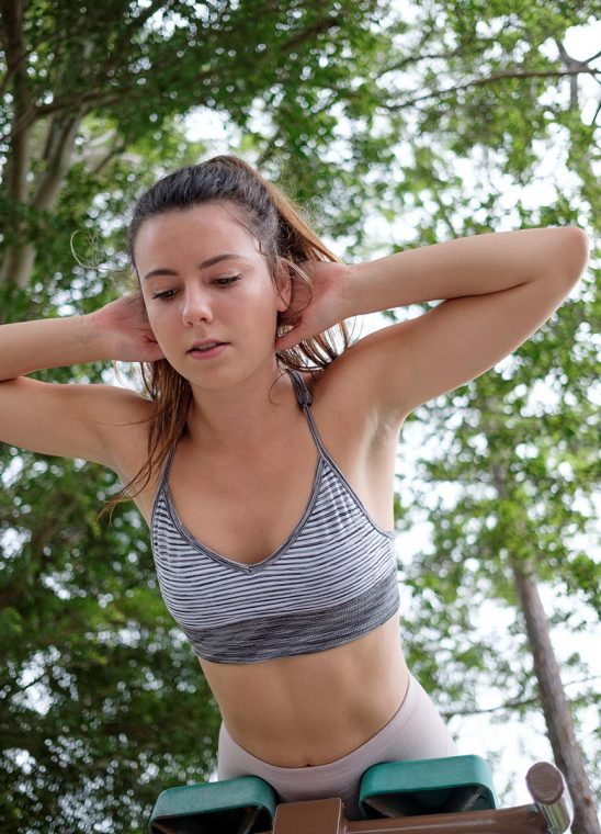 Free stock photo Young woman exercising her abs on a par course outdoors