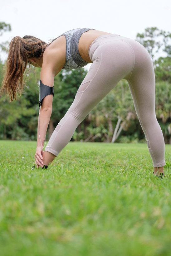 Free stock photo View from behind of a woman stretching before jogging