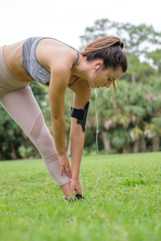 Free stock photo Young woman touching her toes while stretching before a jog