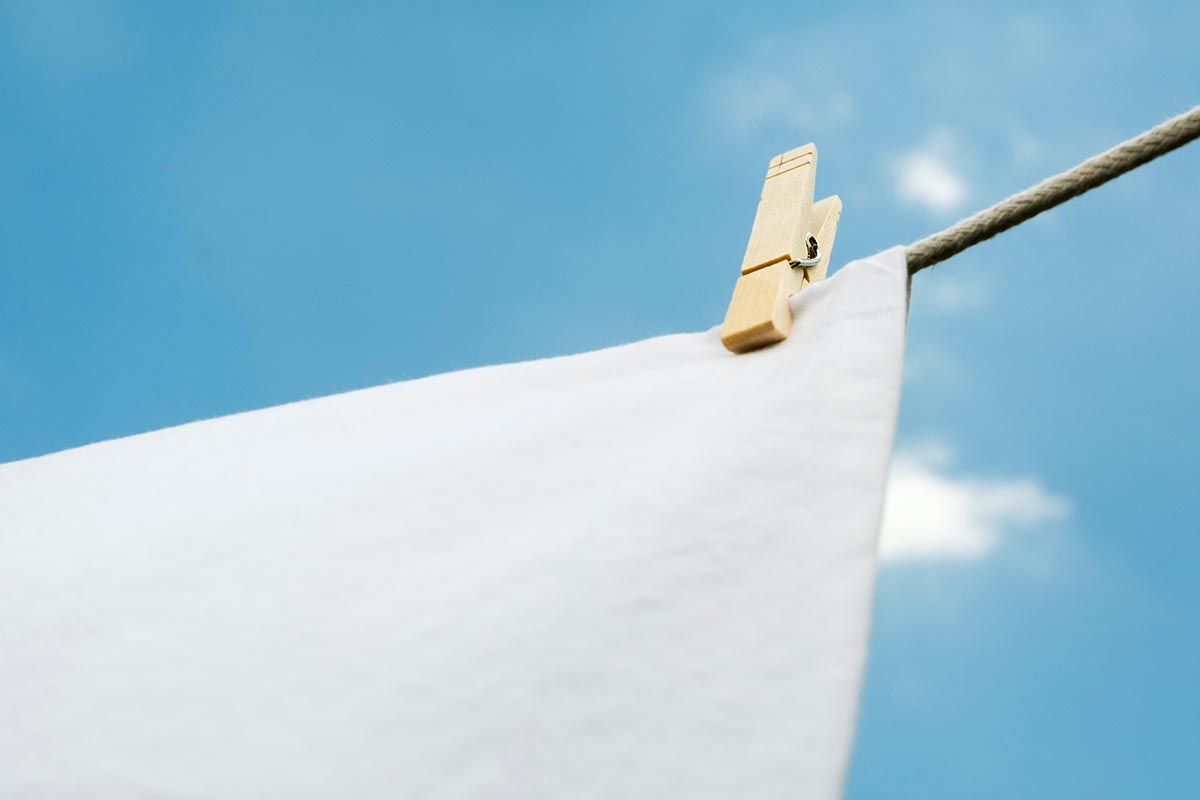 Free stock photo Clothes pin holding a white cloth on a clothesline to dry