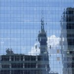 Free stock photo Reflections of city buildings in a glass skyscraper